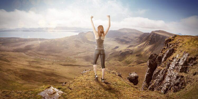 Eine Frau steht mit erhobenen Armen auf der Spitze eines Berges.