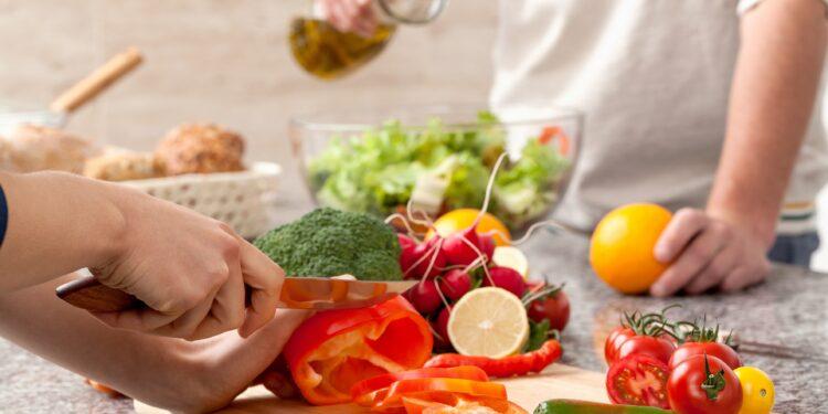 Paar bereitet zusammen einen Salat zu