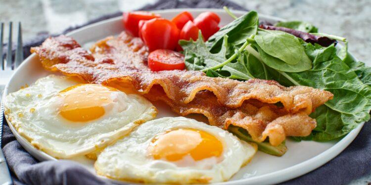 Low Carb Frühstück mit Eiern, Speck, Tomaten und Salat auf einem Teller