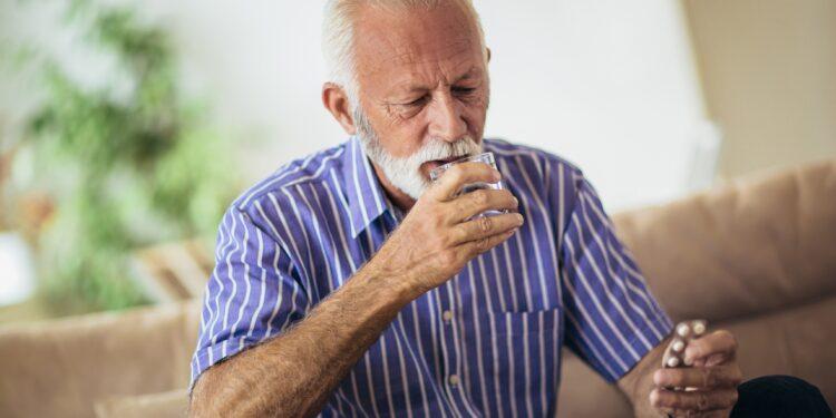 Auf dem Sofa sitzender Senior nimmt eine Tablette ein