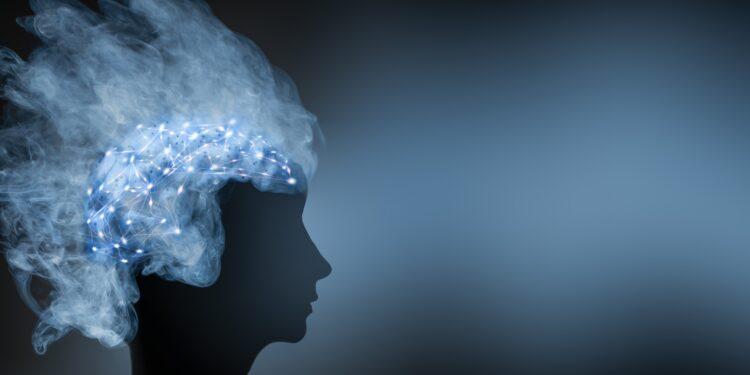 Silhouette eine Kopfes mit erleuchtetem Gehirn.