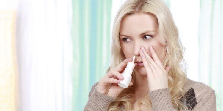 Eine Frau benutzt ein Nasenspray.