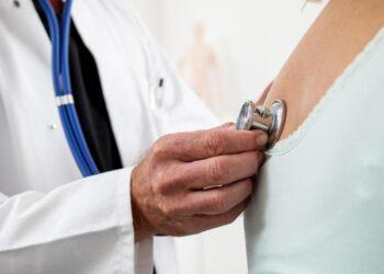 Ein Arzt überprüft die Lungenfunktion und den Herzschlag einer Patientin.