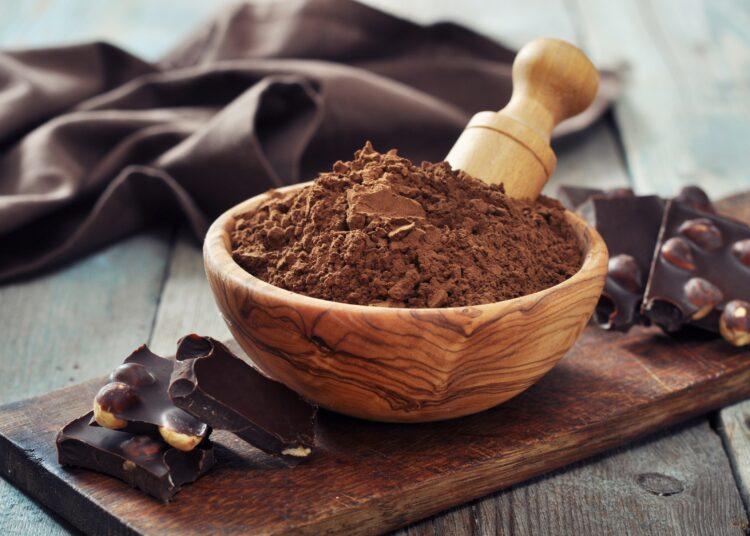 Carobpulver in einer Holzschüssel neben Schokolade auf einem Tisch