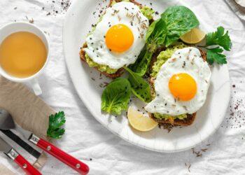 Gebratene Eier auf Brotscheiben mit Avocado neben einer Tasse Tee