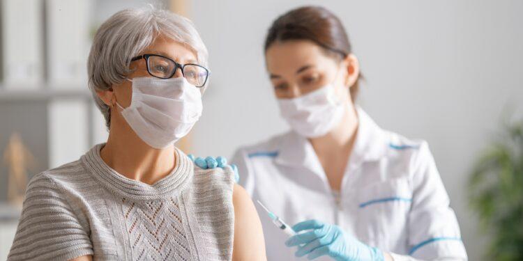 Ärztin impft eine Seniorin in den Oberarm