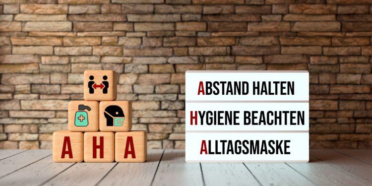 Aufeinander gestapelte Würfel und ein Leuchtkasten, die die AHA-Regeln aufzeigen: Abstand halten, Hygiene beachten, Alltagsmaske