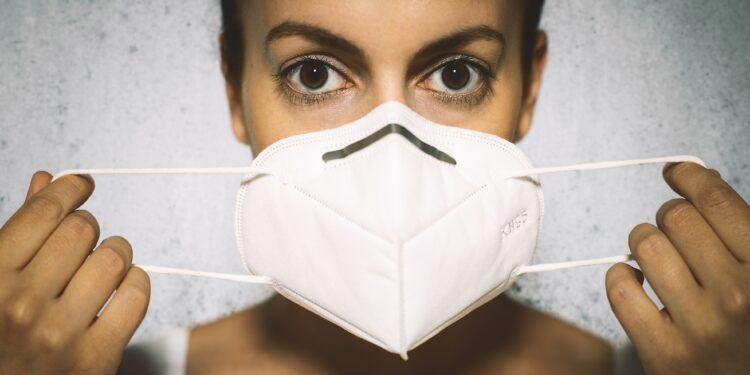 Junge Frau legt eine FFP2-Maske an