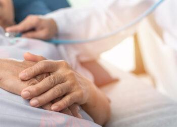 Ältere Frau wird im Krankenhausbett von einem Arzt untersucht
