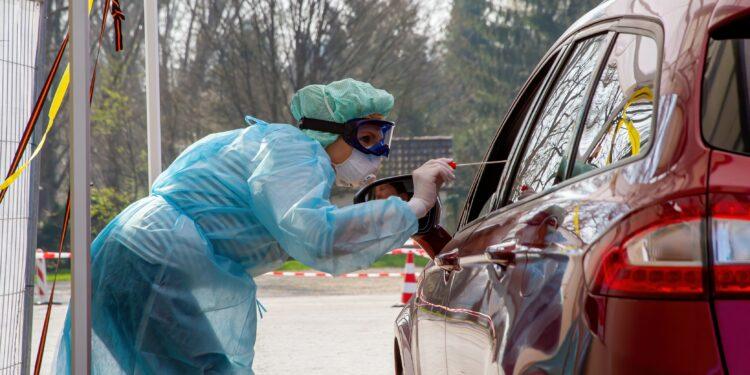Krankenschwester nimmt bei einer im Auto sitzenden Person einen Abstrich für einen Coronavirus-Test