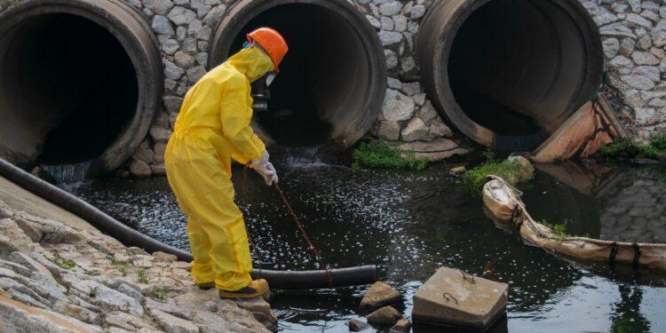 Eine Person im Schutzanzug entnimmt eine Abwasser-Probe.