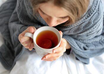 Junge Frau mit einer Tasse Tee im Bett