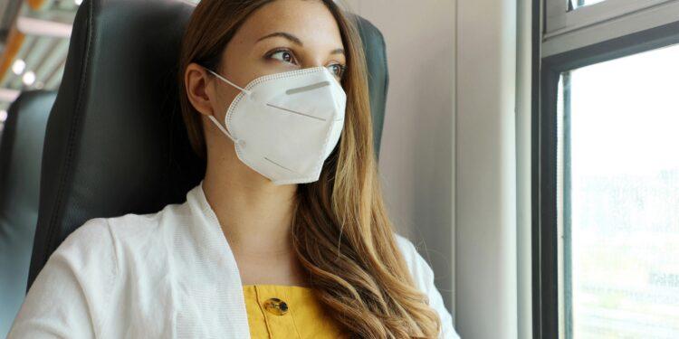 Frau mit FFP2-Maske in einem Zug sieht aus dem Fenster