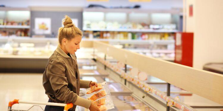 Eine Frau nimmt einen Fisch aus einer Tiefkühltruhe im Supermarkt.
