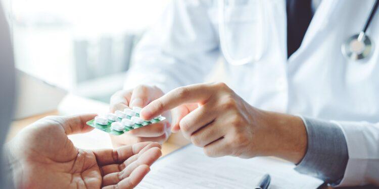 Arzt übergibt Patienten einen Medikamentenblister und deutet mit dem Finger darauf