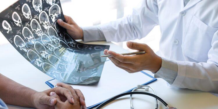 Arzt hält die Röntgenaufnahme eines Gehirns und bespricht das Ergebnis mit einem Patienten