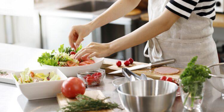 Frau bereitet einen gemischten Salat in einer Küche zu