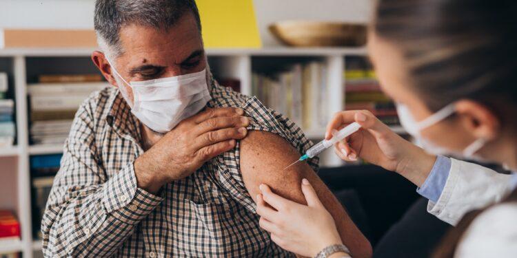 Älterer Mann wird in den Oberarm geimpft