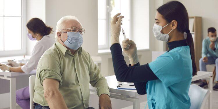 Älterer Mann mit Mund-Nasen-Bedeckung wartet auf eine Impfung, während eine Ärztin die Spritze vorbereitet