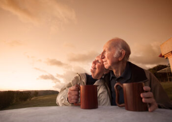 Ein altes Pärchen sitzt Arm in Arm draußen in betrachtet den Sonnenaufgang.