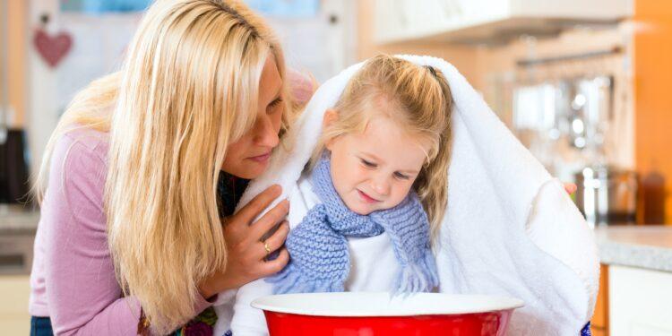 Mutter hilft Tochter beim Inhalieren von Wasserdampf