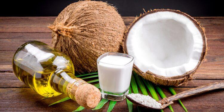 Frische Kokosnüsse, Kokosöl und Koksmilch auf einem Tisch