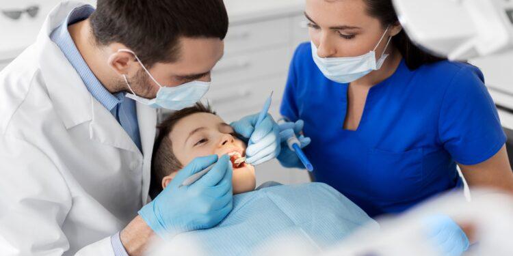Zahnarzt untersucht Zähne eines Kindes