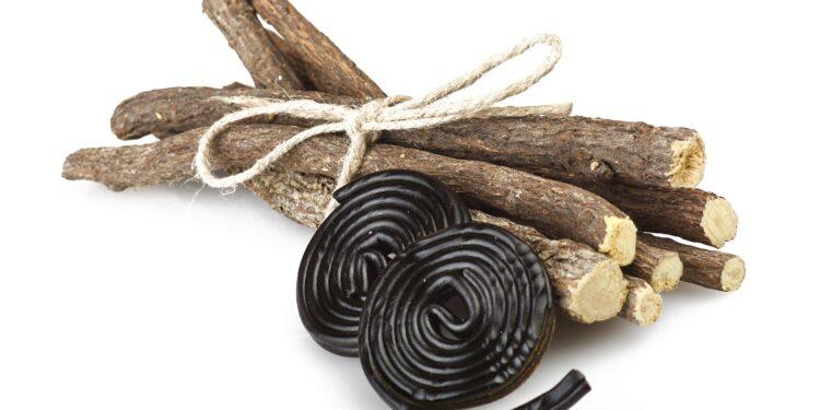 Süßholzwurzel und Lakritz vor einem weißen Hintergrund.