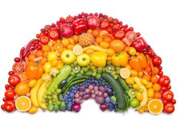Verschiedenfarbige Obst und Gemüsesorten sind in Form eines Regenbogens angeordnet.
