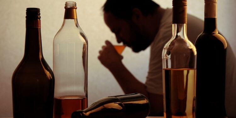 Mann mit verschiedenen Flaschen Alkohol.