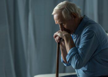 Einsamer alter Mann stützt sich auf Stock.