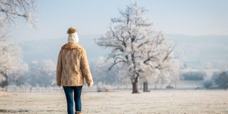 Frau macht einen Spaziergang in winterlicher Landschaft