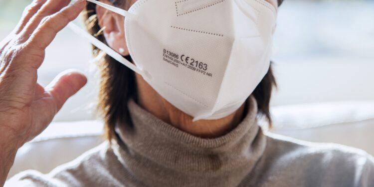 Frau setzt eine FFP2-Maske auf
