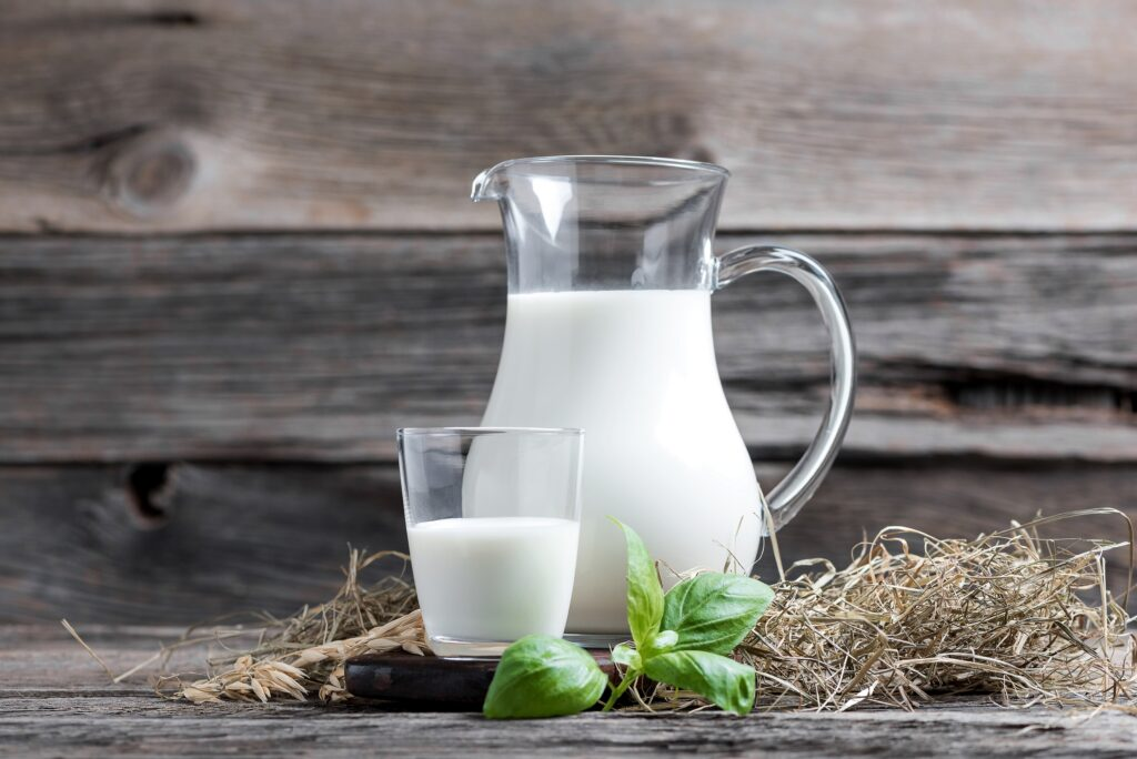 Glas und Karaffe mit Milch.