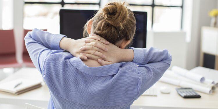 Müde Geschäftsfrau hält ihren Nacken
