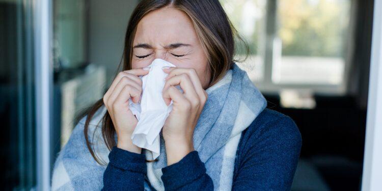 Frau putzt sich die Nase.