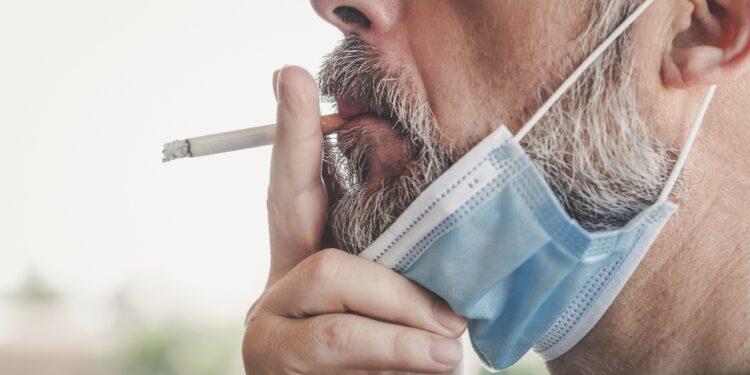 Ein Mann mit heruntergezogener Gesichtsmaske raucht eine Zigarette.