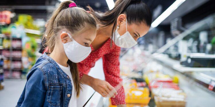 Mutter und Tochter mit Mund-Nasen-Bedeckung beim Einkaufen im Supermarkt