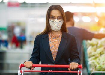 Eine Frau mit Mund-Nasen-Bedeckung mit einem Einkaufswagen im Supermarkt