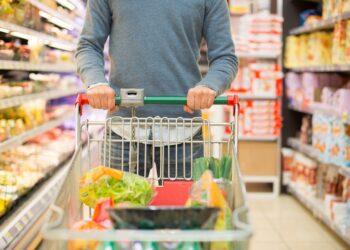 Mann beim Einkaufen im Supermarkt mit vollem Einkaufswagen