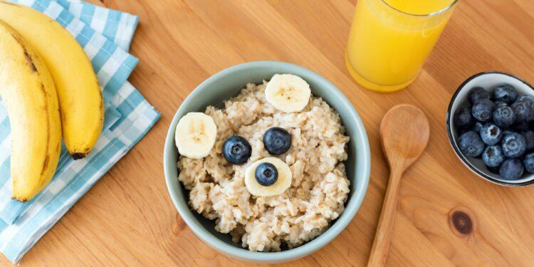 Eine Schüssel mit Porridge und Früchten sowie ein Glas Orangensaft, ein Kochlöffel, Blaubeeren und Bananen auf einem Tisch