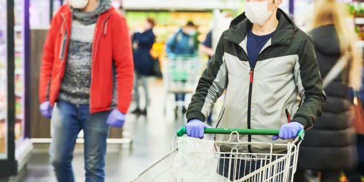 Mann mit Mund-Nasen-Bedeckung und Handschuhen mit Einkaufswagen im Supermarkt
