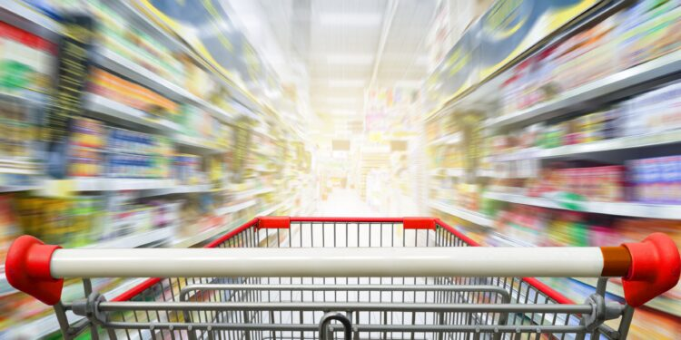 Supermarktgang mit leerem roten Einkaufswagen