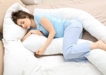 Frau schläft mit Seitenkissen.