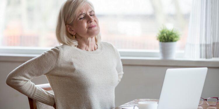 Frau vor Laptop leidet an starken Rückenschmerzen.