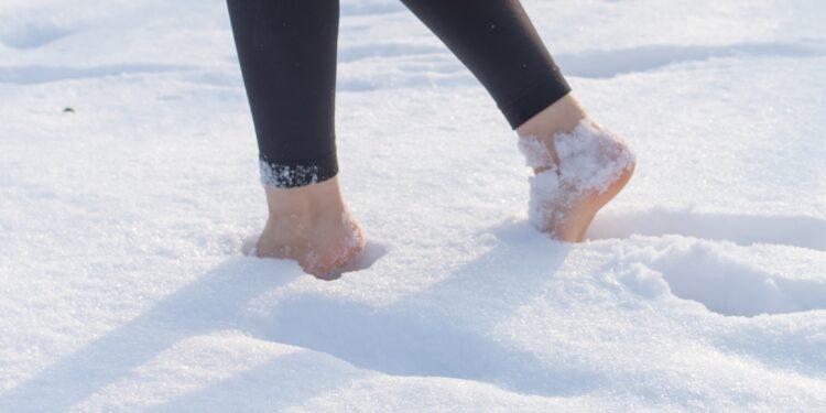 Frau stapft barfuß durch den Schnee
