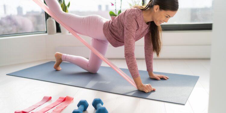 Frau trainiert mit Gewichten und Bändern.