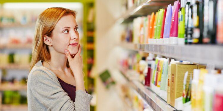 Eine Frau steht vor einem Supermarkt-Regal mit Pflegeprodukten.