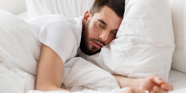 Mann schläft in Bett.