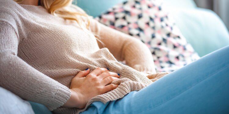 Eine junge Frau sitzt auf dem Sofa und hält ihre Hände an ihren schmerzenden Unterleib